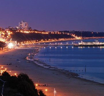 Bournemouth Pier lit up at night from Alum Chine beach